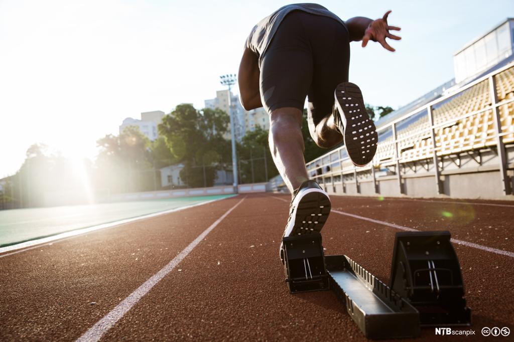 Ung mannlig idrettsutøver sett bakfra på startstreken. Foto.