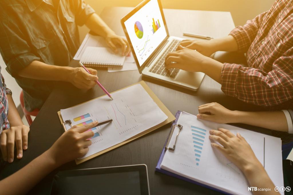 Gruppe mennesker samarbeider om statistikker. Bilde.