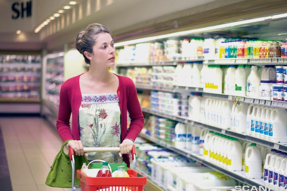 Kvinne handler på supermarked. Foto.