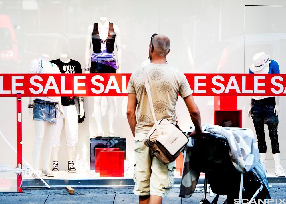 Mann foran butikkvindu med salsplakat. Foto.