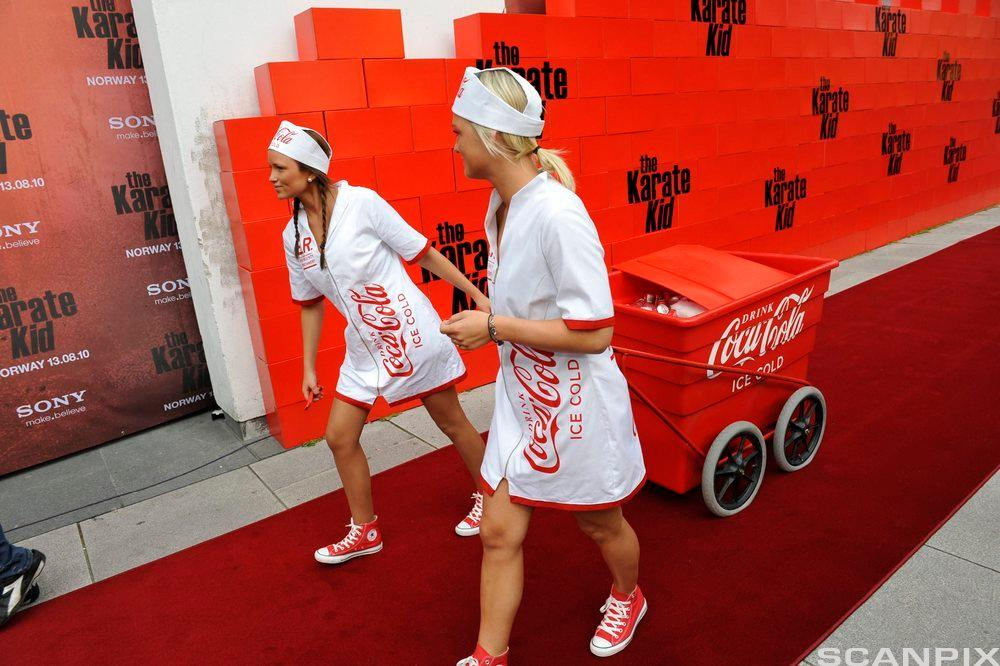To jenter marknadsfører Coca-Cola. Foto.