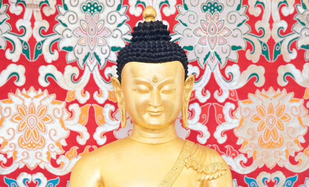 Gullfarget hode og skuldre på en buddhastatue. Foto.