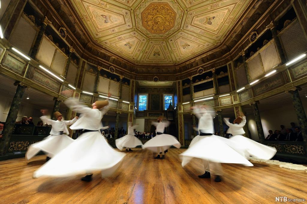 Ei gruppe menn med høge hattar og vide skjørt snurrar rundt i ein dans. Foto.