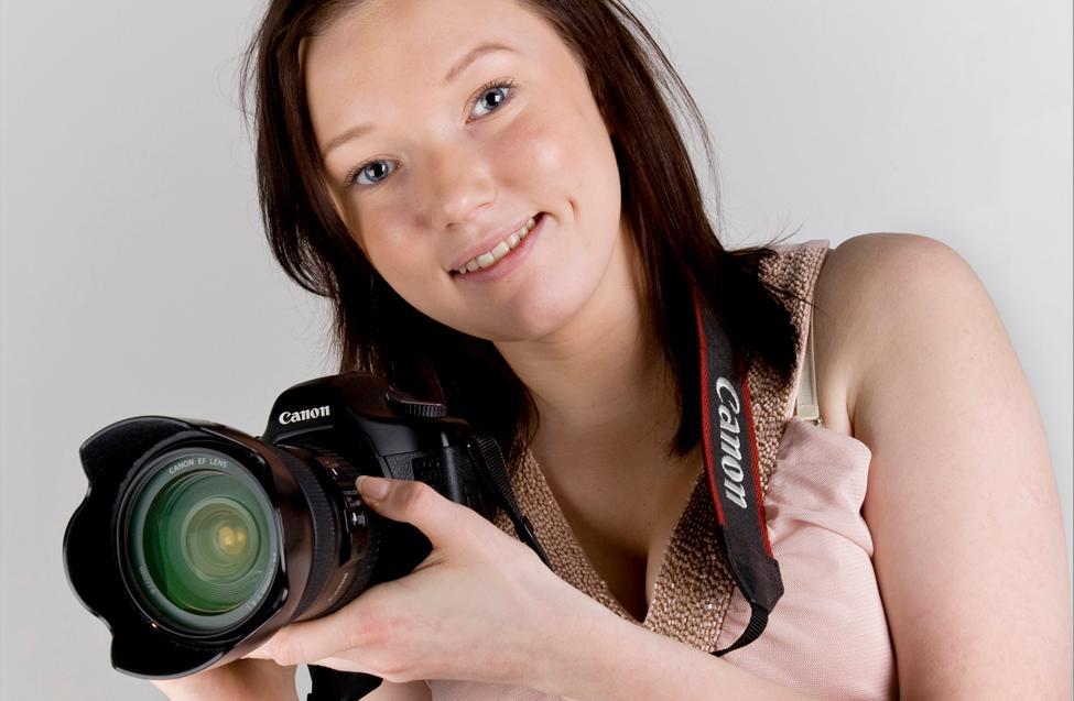 Jente holder speilreflekskamera med stropp rundt halsen. Foto.