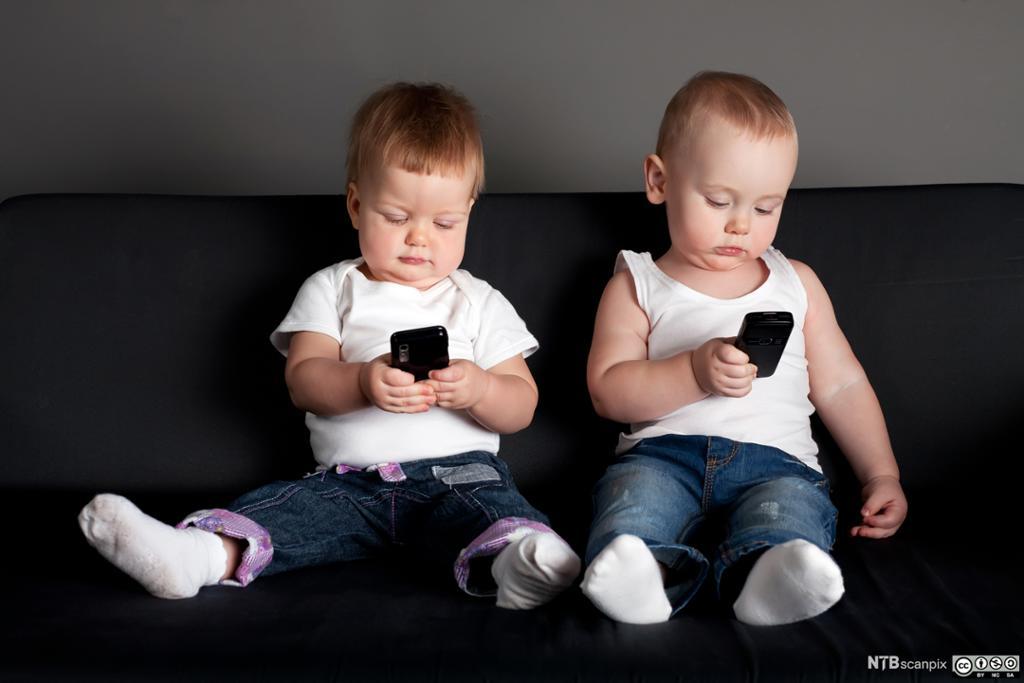 To små barn med hver sin mobiltelefon. Foto.