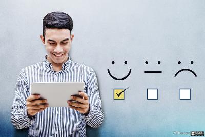 En ung mann ser smilende på et nettbrett. Ved siden av ham er det illustrert et smilefjes, et nøytralt fjes og et surt fjes med avmerkingsbokser under, og det er huket av i boksen under smilefjeset. Illustrasjon.