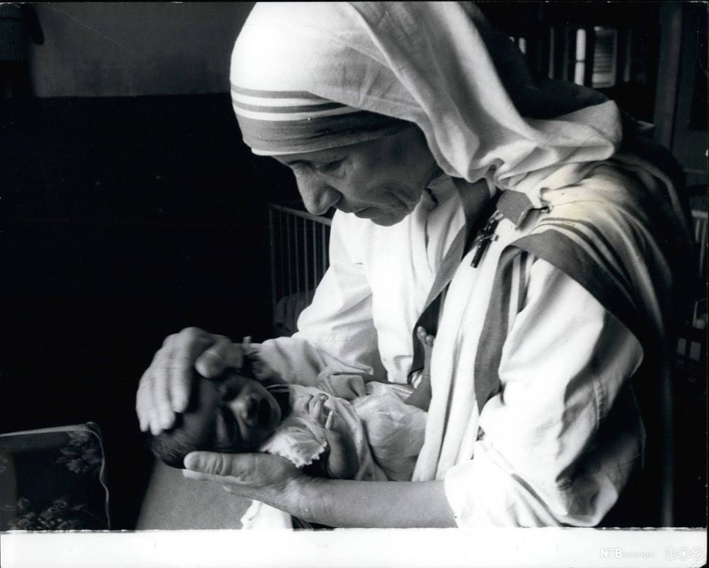 Nonne holder hånden på hodet til et spebarn. Foto.
