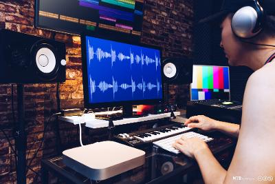 Ung mann gjør etterarbeid på lyd i studio. Bilde.