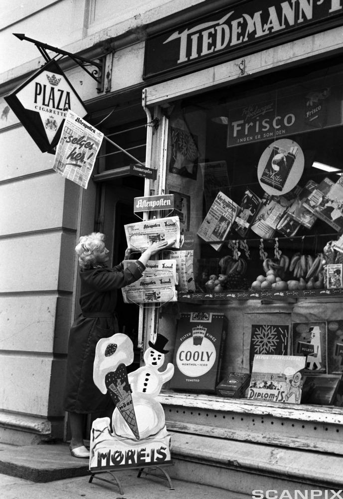 Bilde av en kvinne som plasserer Aftenposten i et avisstativ utenfor en kiosk 19. juni 1962.