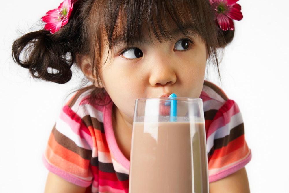 Jente drikker sjokolademelk.Foto
