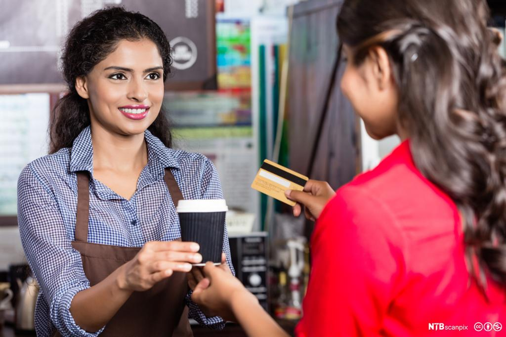 Kvinne betaler kaffe med kredittkort. Foto.