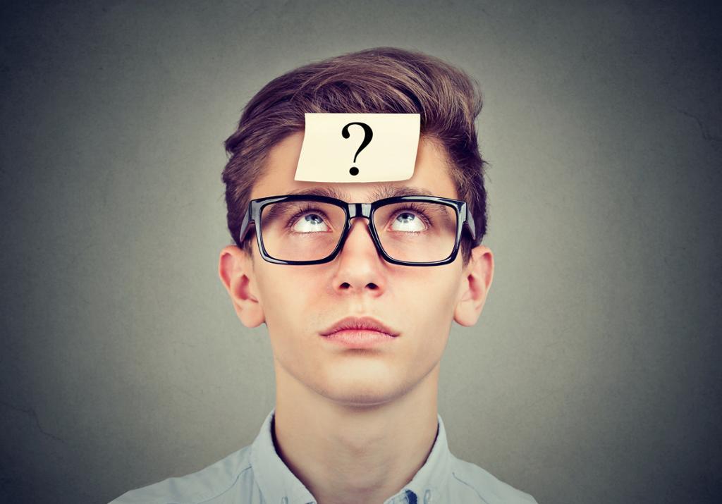 Tenkende mann med briller og spørsmålstegn i pannen. Foto.