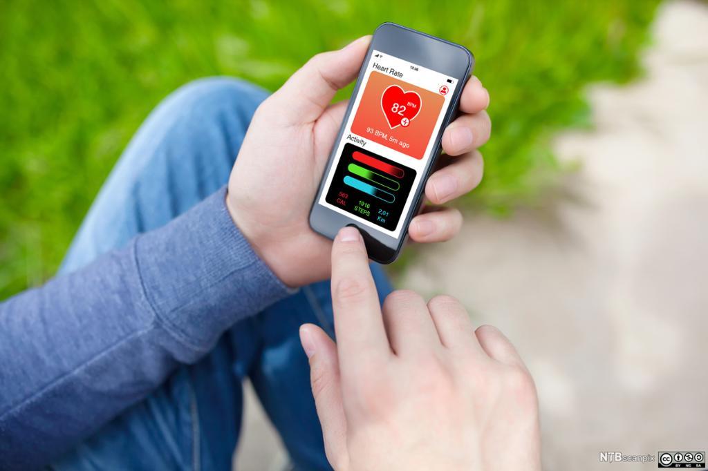 Person holder en mobiltelefon med en helse app. Foto.