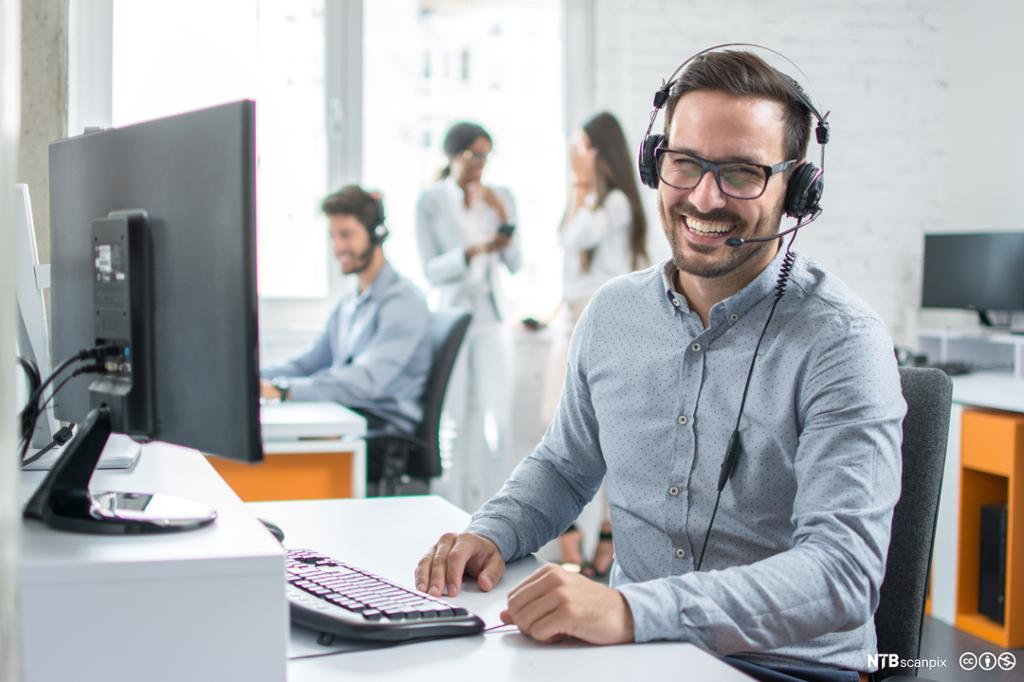 Mann som sitter foran en pcskjerm med headset på hode