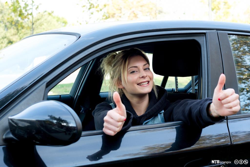 Ung kvinne med tomlene opp i en bil
