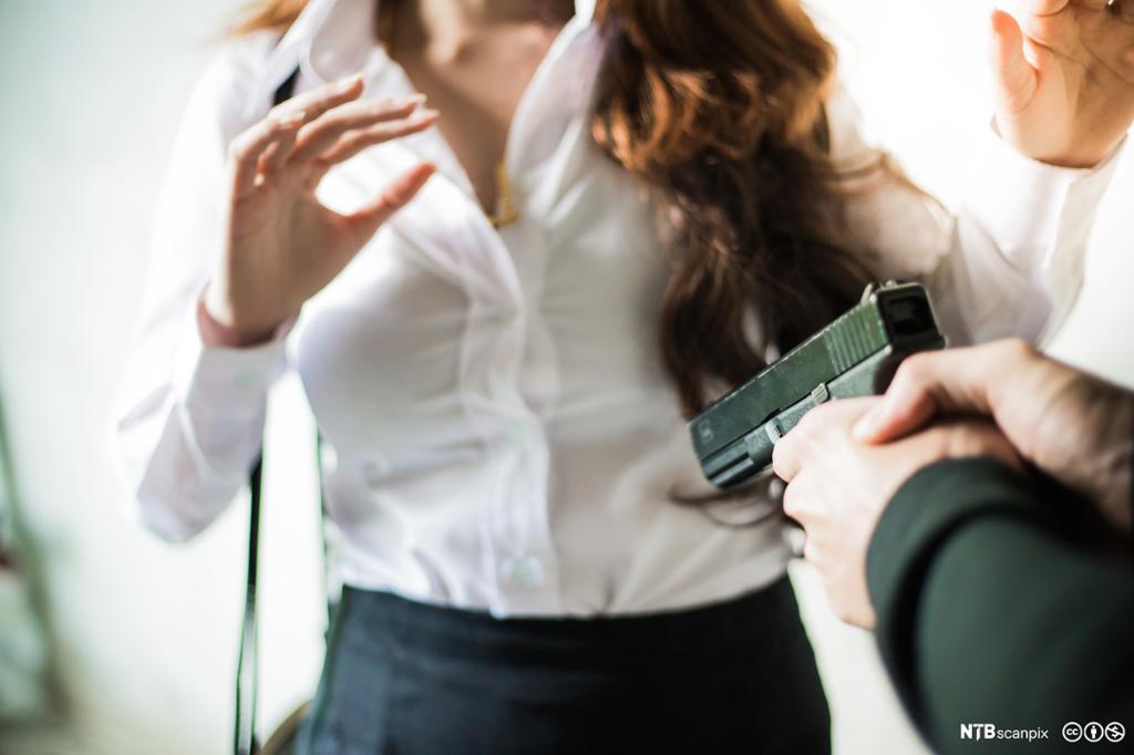 Mann med pistol truer en kvinne. Overfall. Foto.