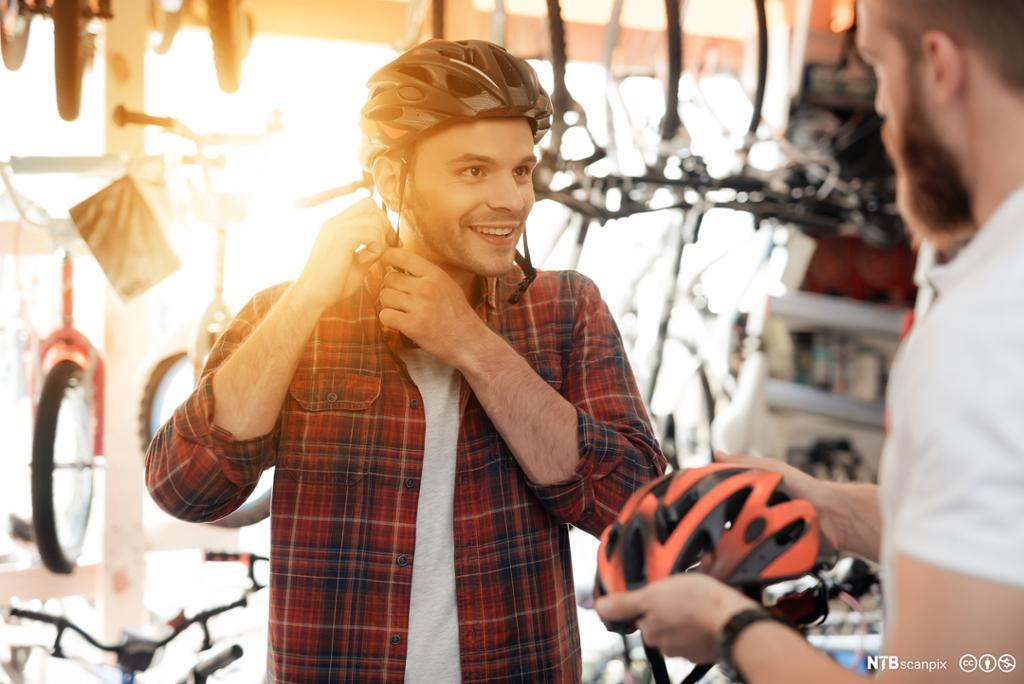 Mann som prøver sykkelhjelmer i en sportsbutikk