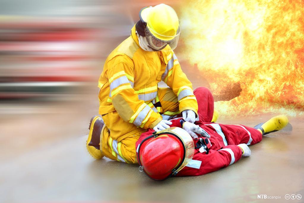 En brannmann redder en kollega. Foto.