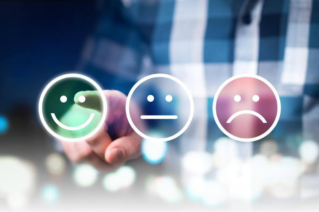 Forretningsmann gir vurdering og gjennomgang med lykkelige, nøytrale eller triste ansiktsikoner. Foto.
