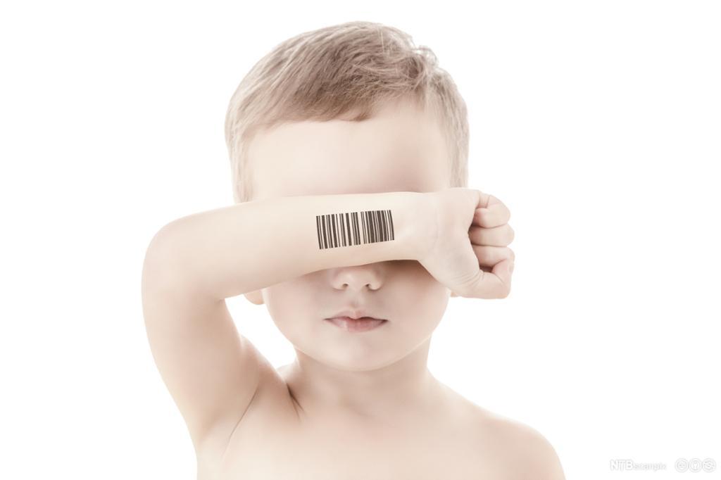 Lyst barn holder arm med strekkode foran øynene. Foto.
