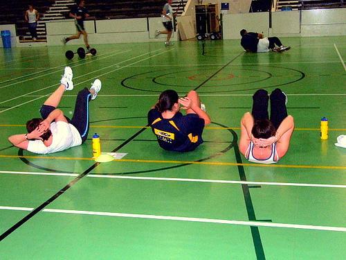 Tre damer trener styrke. Foto.