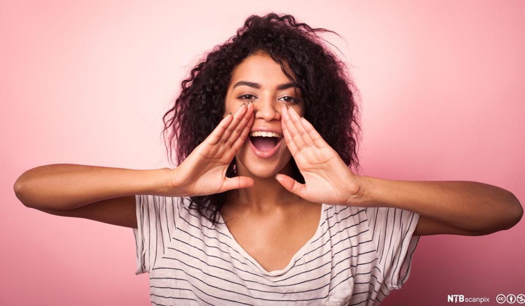 Jente holder hendene opp til munnen og roper. Foto.