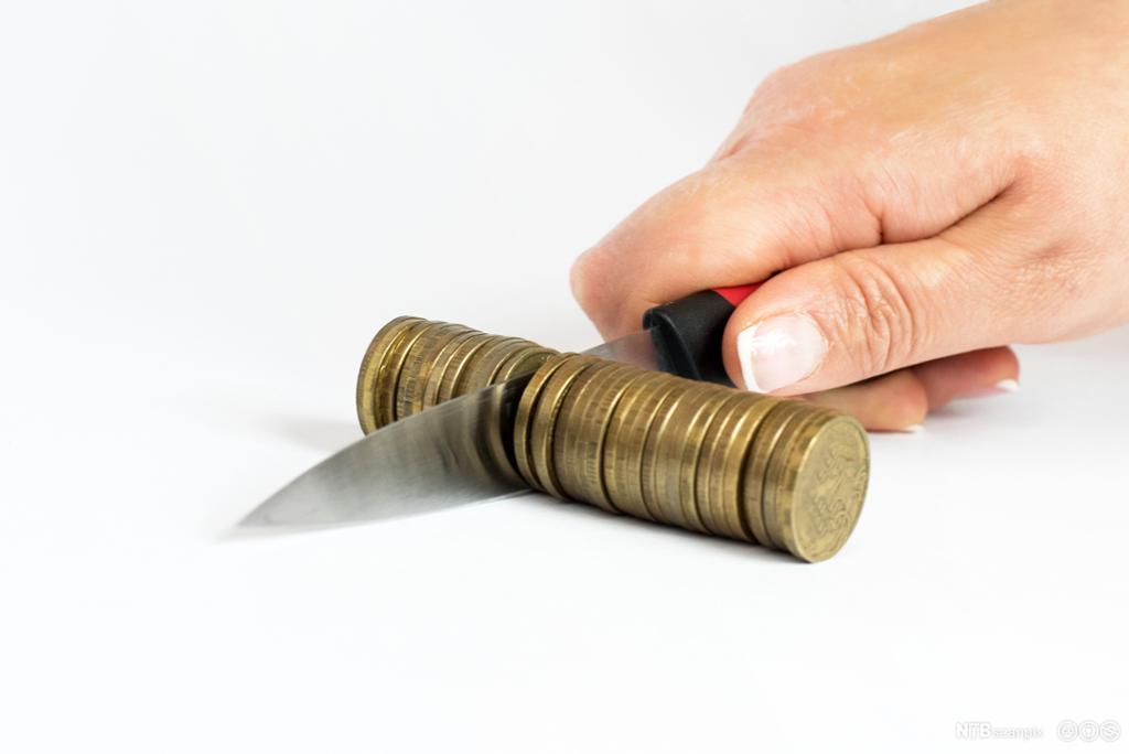 Kniv kutter en haug med mynter. Foto.