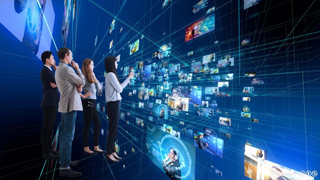 Gruppe av mennesker som bruker futuristisk grensesnitt. Foto