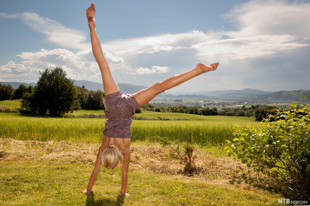 Jente som står på hendene utandørs ein solfylt dag. Foto.
