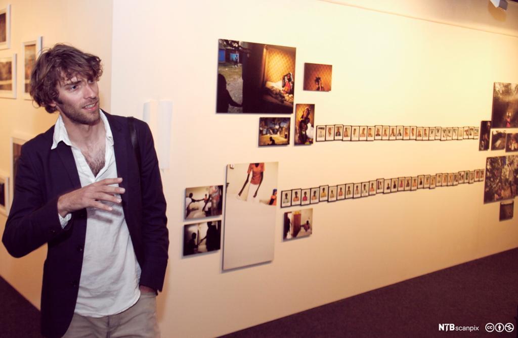 Jonas Bendiksen stiller ut bildene sine på en vegg. Bilde.