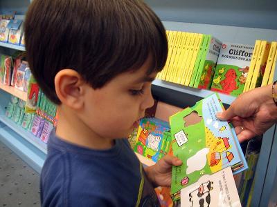 Barn som blar i en bok. Foto.