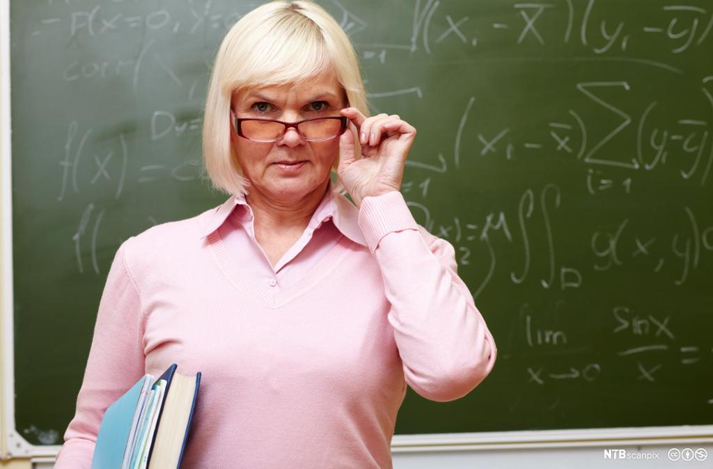 Streng lærer foran tavle. Foto.