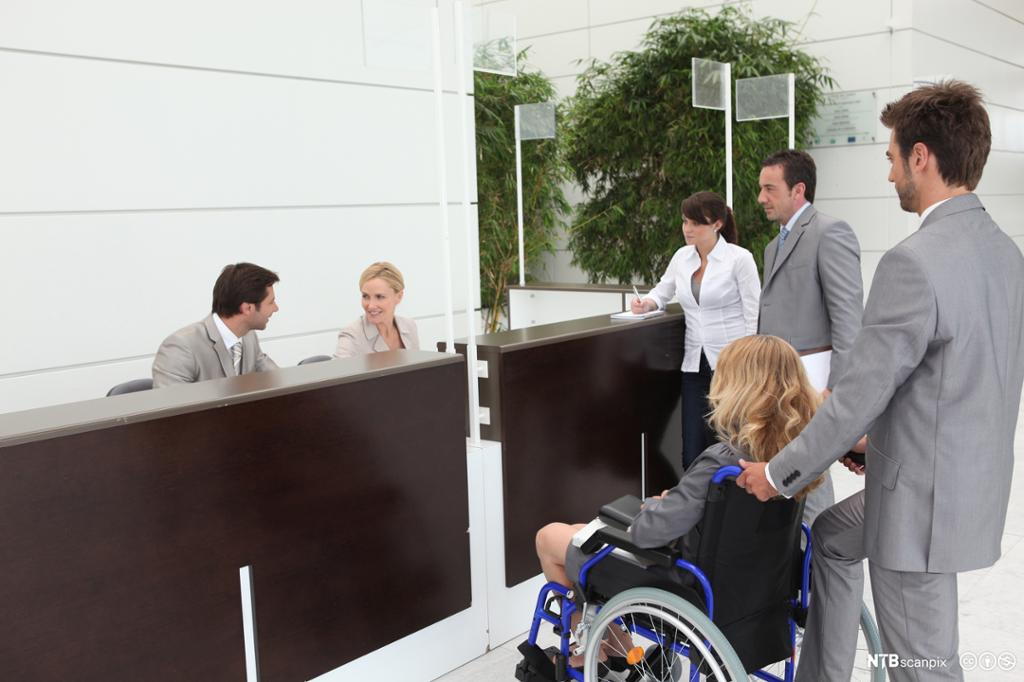 Forretningskvinne i rullestol med kolleger i hotellresepsjonen. Foto.