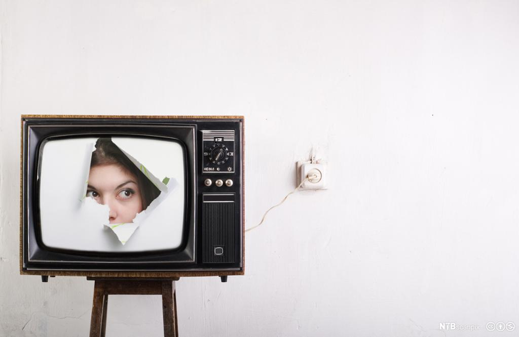 Ansikt titter frem i et fjernsynsapparat. Bilde.