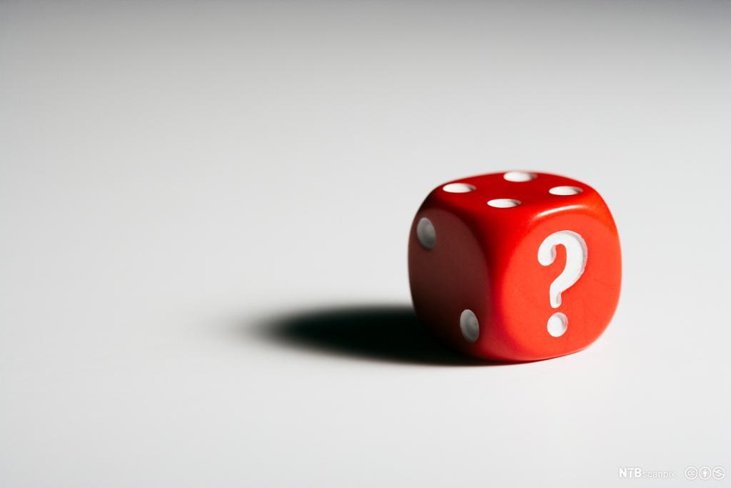 Et fotografi av en terning med et spørsmålstegn.