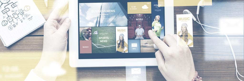 To hender som holder en Ipad. På skjermen på Ipaden er det flere små fargerike bilder. Ved siden av Ipaden ligger en notatbok og et headset. Foto.