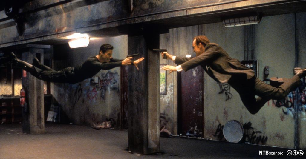 To menn svever liggende i løse luften. De peker mot hverandre med en pistol. Foto.