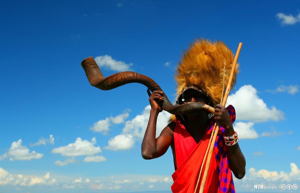 Masaikriger som spiller på tradisjonelt horn. Foto.