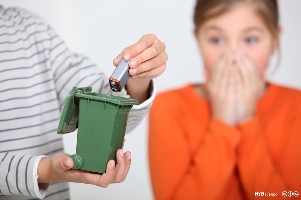 Jente holder hendene foran munnen når gutt kaster batteri i liten søppelkasse. Foto.