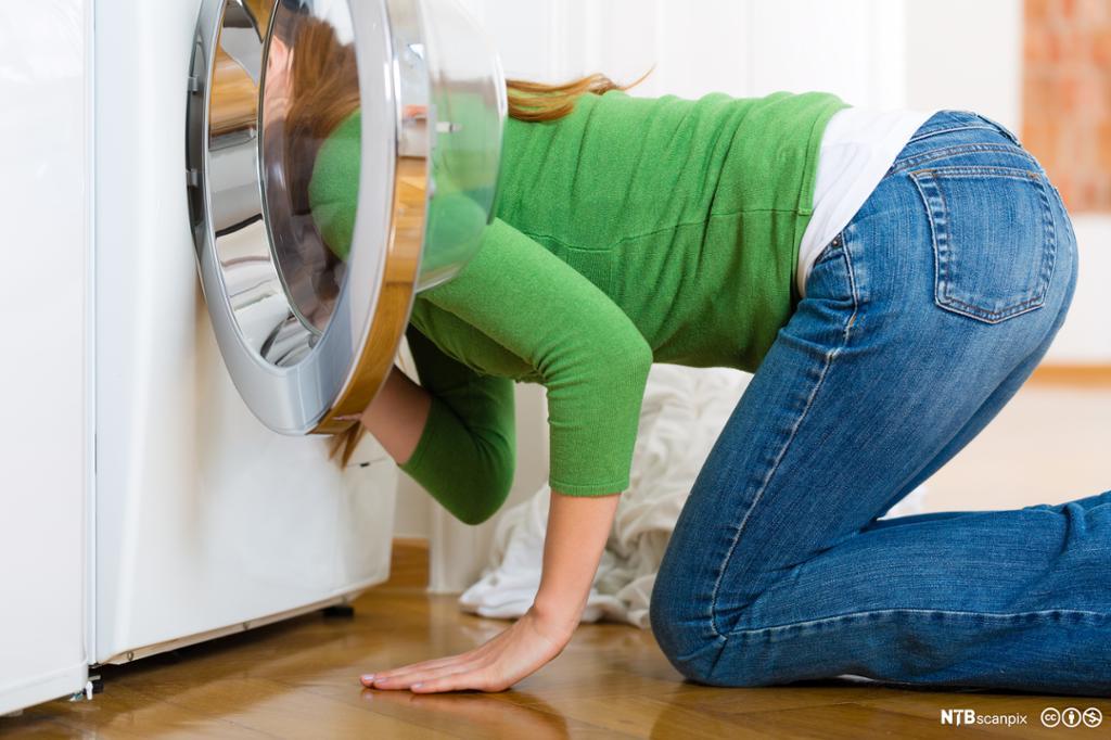 Et fotografi av en kvinne som ser inn i en vaskemaskin.