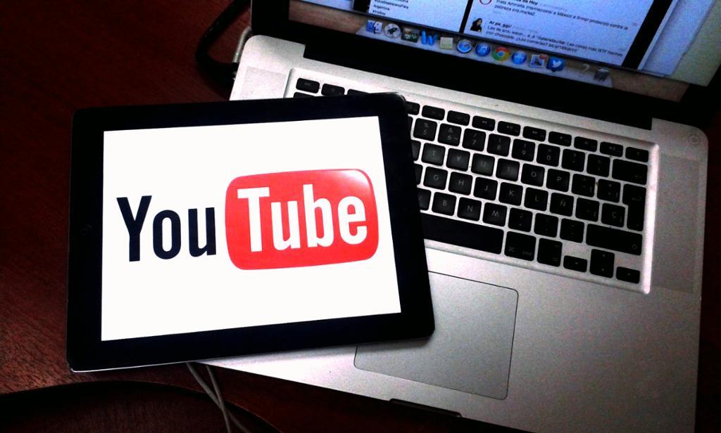 Et nettbrett oppå en pc hvor YouTube-logoen dekker nettbrettet. Foto.