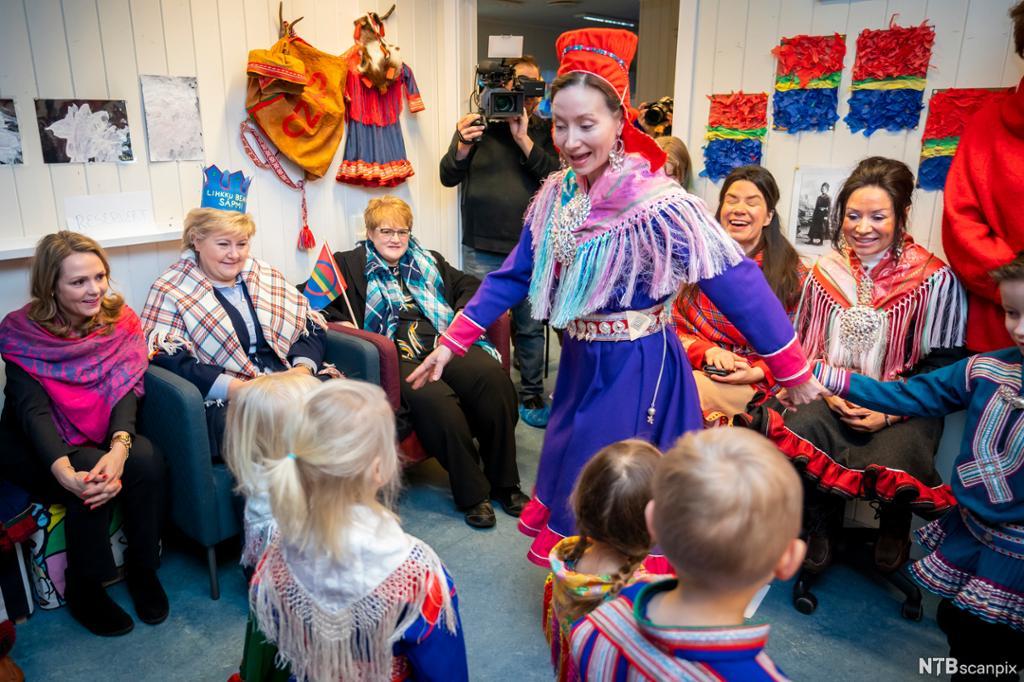 En kvinne kledd i en tradisjonell samisk drakt, danser, mens barn og voksne ser på. Foto.