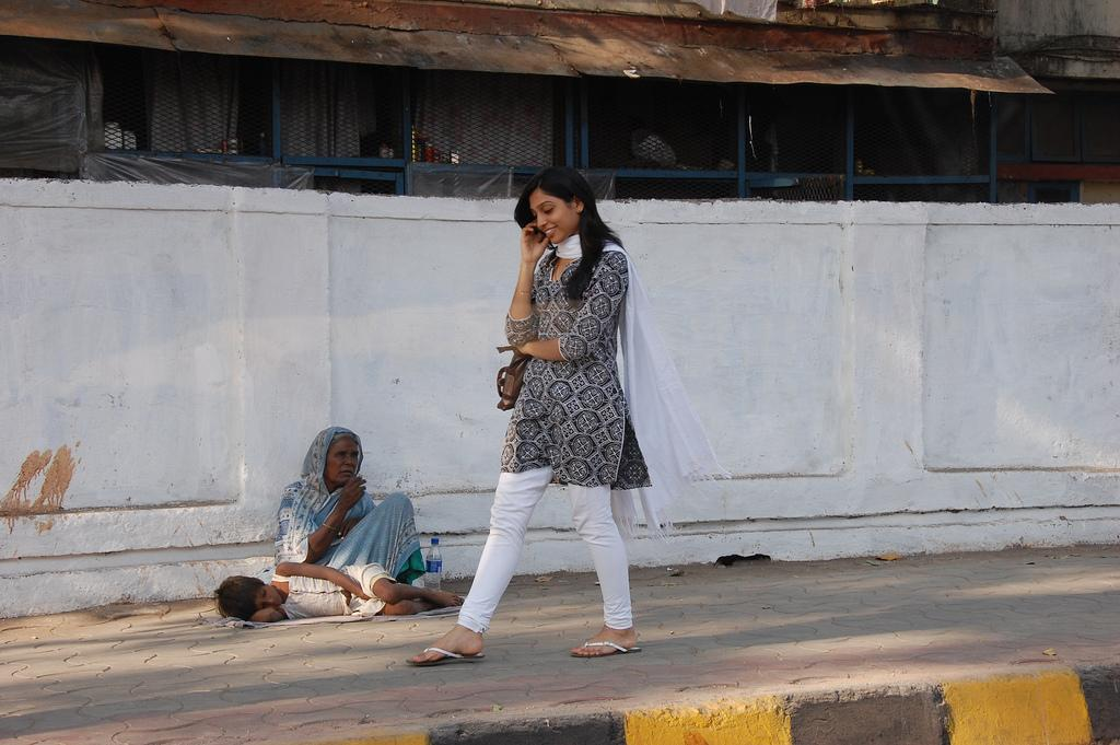 Woman talking on the phone while walking past a homeless woman. Photo.