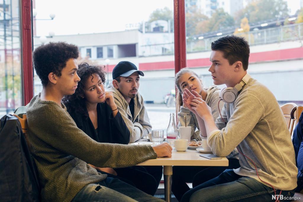 Fem ungdommar snakkar saman rundt eit bord. Foto.