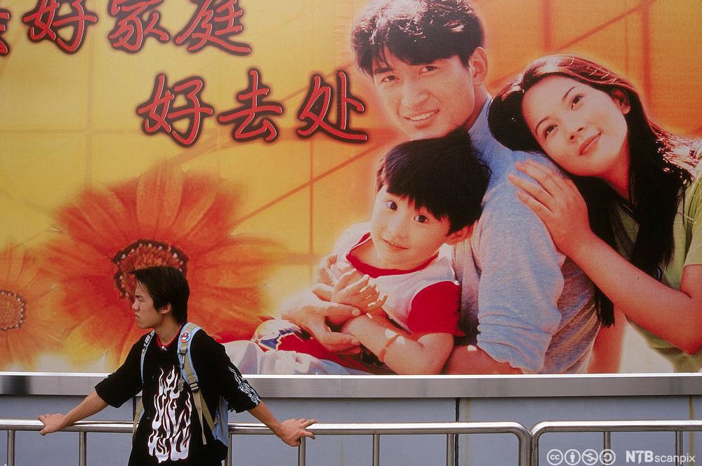En ung mann i Kina står under en plakat som viser en familie med ett barn. Foto.