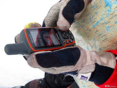 Person med hansker og med kart rundt halsen holder en GPS-sender. Foto.