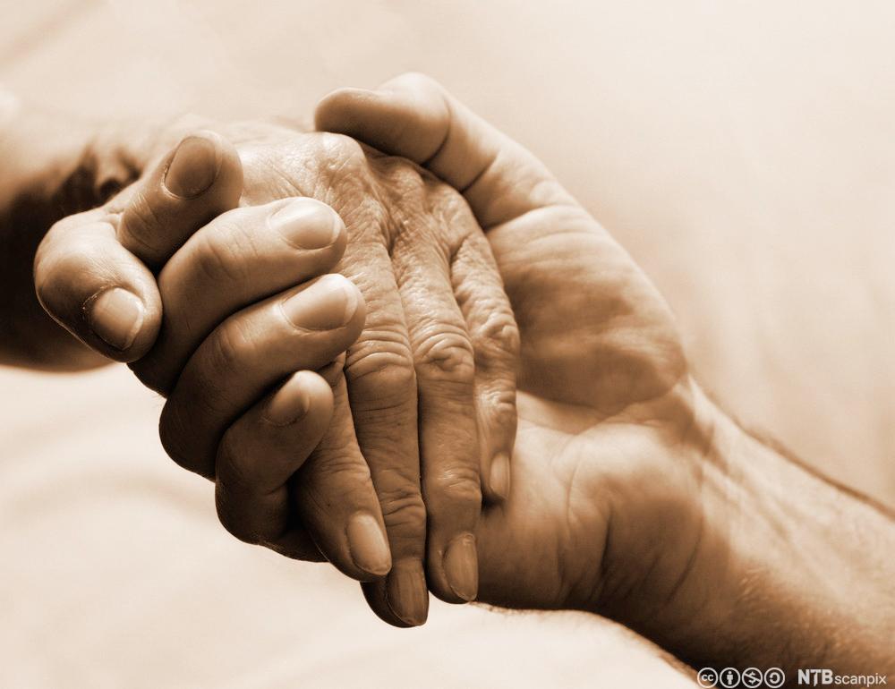 To personer holder hender. Foto.