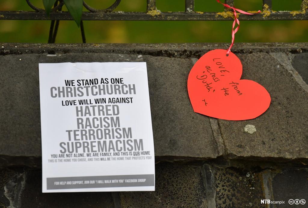 Plakat og rødt hjerte med tekst som fordømmer terrorisme og rasisme. Foto.