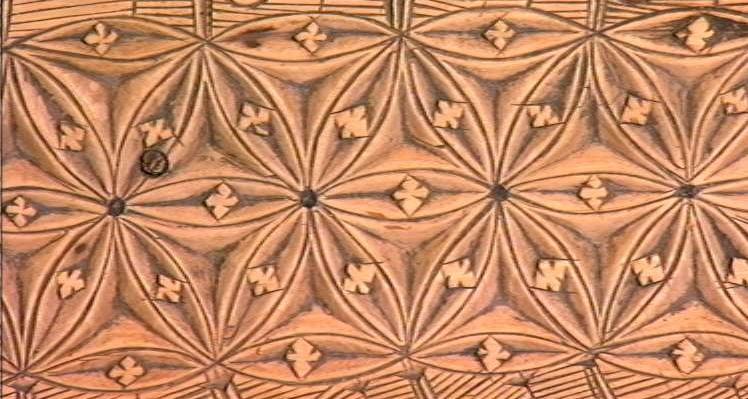 Nærbilde av geometrisk mønster skåret ut i tre. Foto.