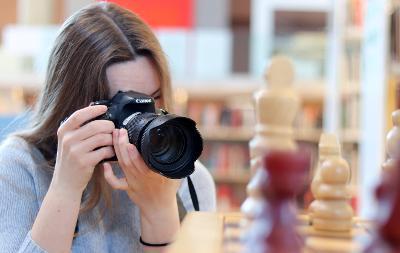 En elev fotograferer sjakkbrikker. Kameraet og eleven er i fokus. Sjakkbrikkene i forgrunnen er ikke i fokus, heller ikke bokhyllene bakerst i rommet der eleven befinner seg. Foto.